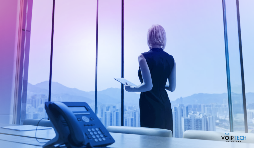 a woman in corporate attire with voip telephone system behind her